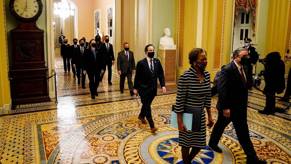 Clerk of the House Cheryl Johnson along with acting House Sergeant-at-Arms Tim Blodgett, lead the Democratic House impeachment managers as they deliver to the Senate the article of impeachment. (AP Photo/Susan Walsh)
