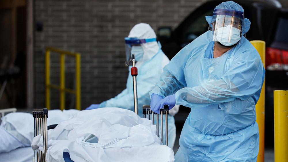 Medical workers wearing personal protective equipment wheel bodies to a refrigerated trailer serving as a makeshift morgue at Wyckoff Heights Medical Center, April 6, 2020, in Brooklyn (AP Photo/John Minchillo)
