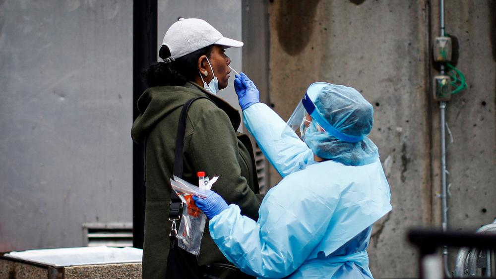 A patient is given a COVID-19 test by a medical worker outside Brooklyn Hospital Center, March 29, 2020 (AP Photo)