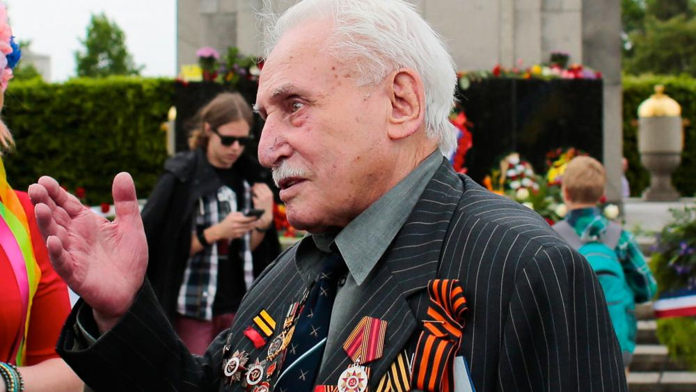 In this Friday, May 8, 2015 file photo, Soviet war veteran David Dushman, 92, center, speaks to people holding Ukrainian flags as he attends a wreath laying ceremony at the Russian War Memorial in the Tiergarten district of Berlin, Germany.  (AP Photo/Mar