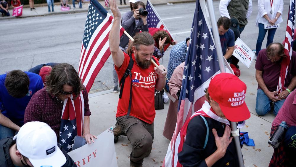 Supporters of President Donald Trump pray near the state capitol, Nov. 7, 2020 in Atlanta. (AP Photo/John Bazemore)