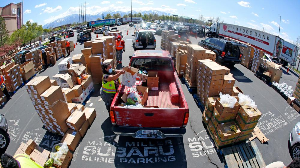 Cars line up for food at the Utah Food Bank's mobile food pantry at the Maverik Center, April 24, 2020, in West Valley City, Utah. As coronavirus concerns continue, the need for assistance has increased. (AP Photo/Rick Bowmer)