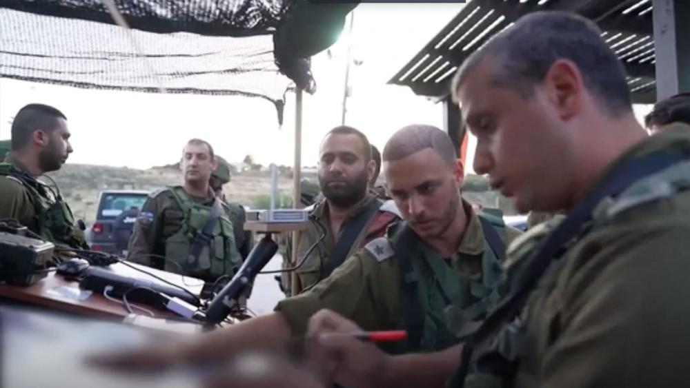 Israeli security forces look at maps in search for gunmen who opened fire on Israeli civilians on Sunday.