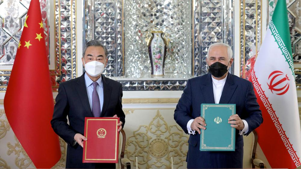 Iranian Foreign Minister Mohammad Javad Zarif, right, and his Chinese counterpart Wang Yi, pose for photos after the ceremony of signing documents, in Tehran, Iran, Saturday, March 27, 2021. (AP Photo/Ebrahim Noroozi)