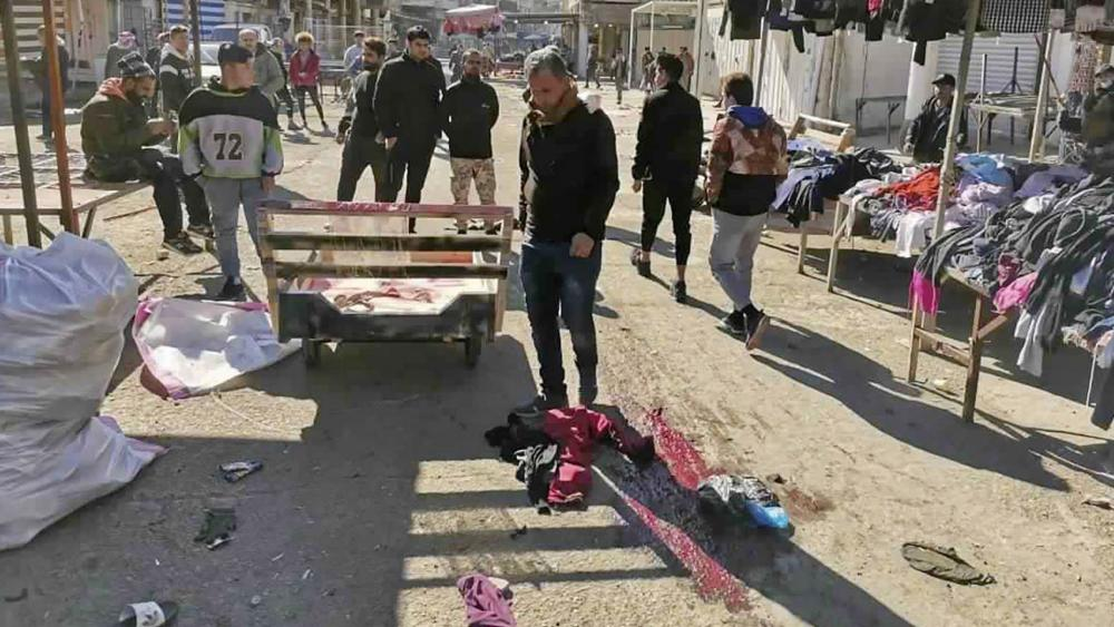 People and security forces gather at the site of a deadly bomb attack in Baghdad's bustling commercial area, Iraq, Thursday, Jan. 21, 2021. Twin suicide bombings hit Iraq's capital Thursday killing and wounding civilians, police and state TV said. (AP Pho