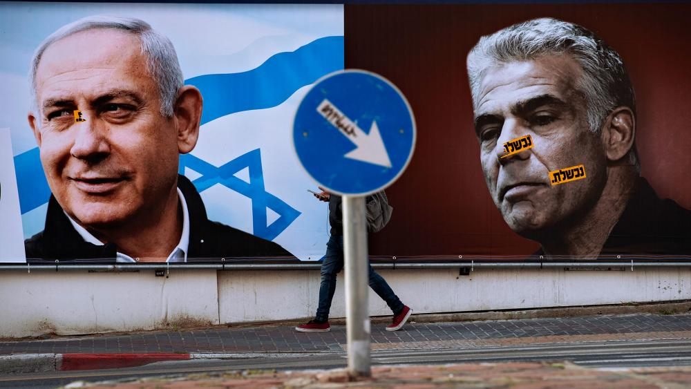 An election campaign billboard for the Likud party shows a portrait of its leader Prime Minister Benjamin Netanyahu, left, and opposition party leader Yair Lapid.  (AP Photo/Oded Balilty)