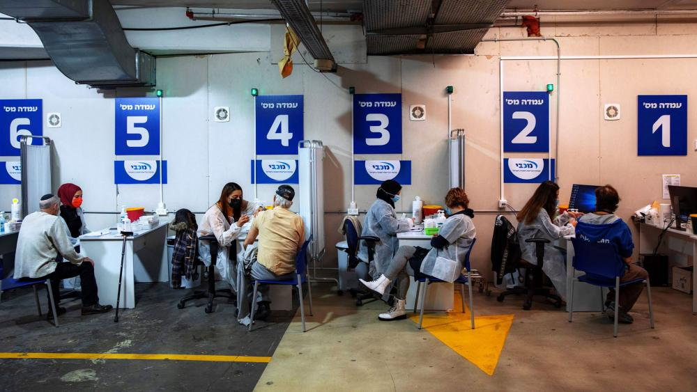Israelis receive a Pfizer-BioNTech COVID-19 vaccine from medical professionals at a vaccination center set up on a mall parking lot in Givataim, Israel.  (AP Photo/Oded Balilty)