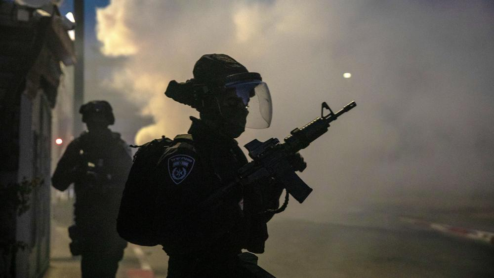 Israeli forces run during clashes with Israeli Arabs in the Israeli mixed city of Lod, Israel, Tuesday, May 11,2021. (AP Photo/Heidi Levine)