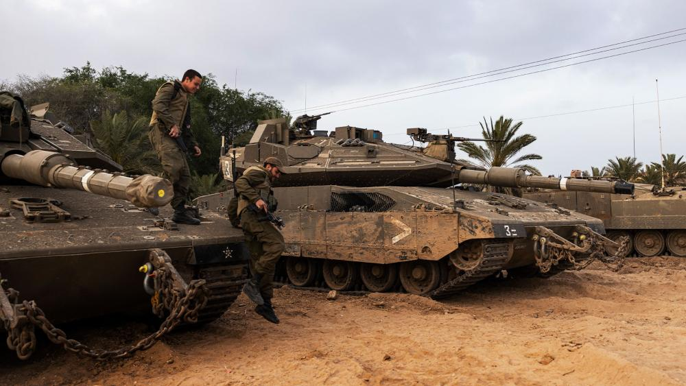 Israeli soldiers jump from a tank in a front position near the Israel Gaza border, Saturday, April 24, 2021. (AP Photo/Tsafrir Abayov).