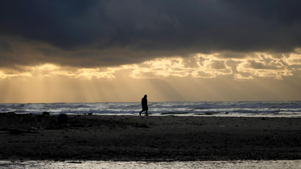 AP/A person walks on the beach as heavy clouds gather over the Mediterranean Sea and the Alexander River, in Hefer Valley, Israel, Thursday, Jan. 9, 2020.