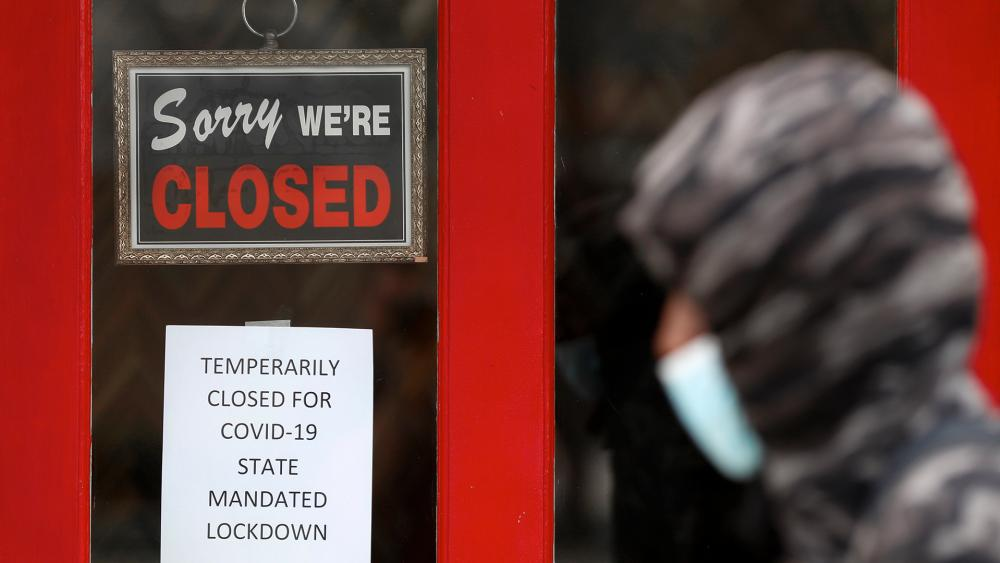 A pedestrian walks by The Framing Gallery, closed due to the COVID-19 pandemic, in Grosse Pointe, Mich. (AP Photo/Paul Sancya, File)