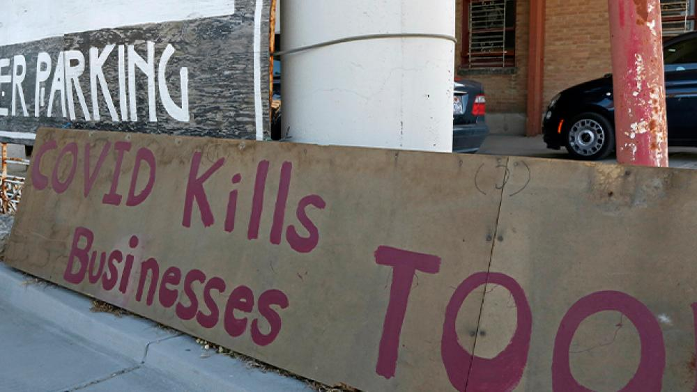 """A """"Covid kills businesses too"""" sign is shown outside Euro Treasures Antiques, May 8, 2020, in Salt Lake City. (AP Photo/Rick Bowmer)"""