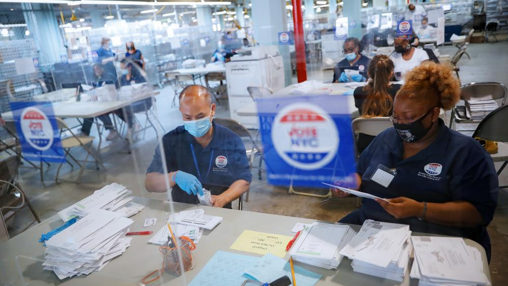 Workers wear personal protective equipment and are separated in pairs from fellow employees by plastic shields as they process ballots at a Board of Elections facility, Wednesday, July 22, 2020, in New York. (AP Photo/John Minchillo)