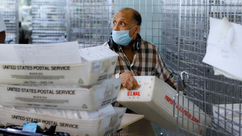 A worker gathers ballots from security cages before they are checked at a Board of Elections facility (AP Photo/John Minchillo)