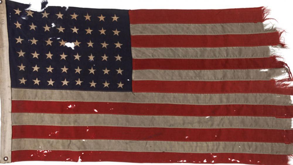 This 48-star American flag tattered by the wind and torn by German machine gun bullets on D-Day was returned to the US Thursday. ( Image credit: Heritage Auctions, HA.com)