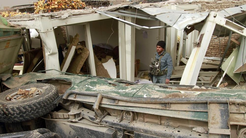 A security official inspects the site of a car bomb attack in Herat province, west of Kabul, Afghanistan, Saturday, March 13, 2021.  (AP Photo/Hamed Sarfarazi)