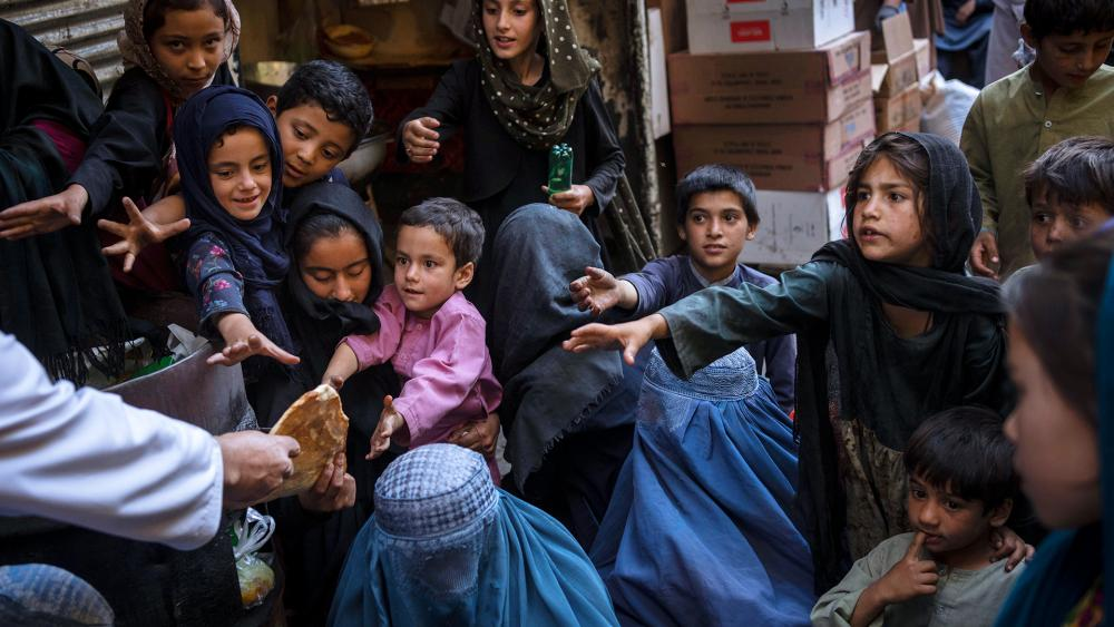 Afghan women and children receive bread donations in Kabul's Old City, Afghanistan, Sept. 16, 2021. (AP Photo/Bernat Armangue)