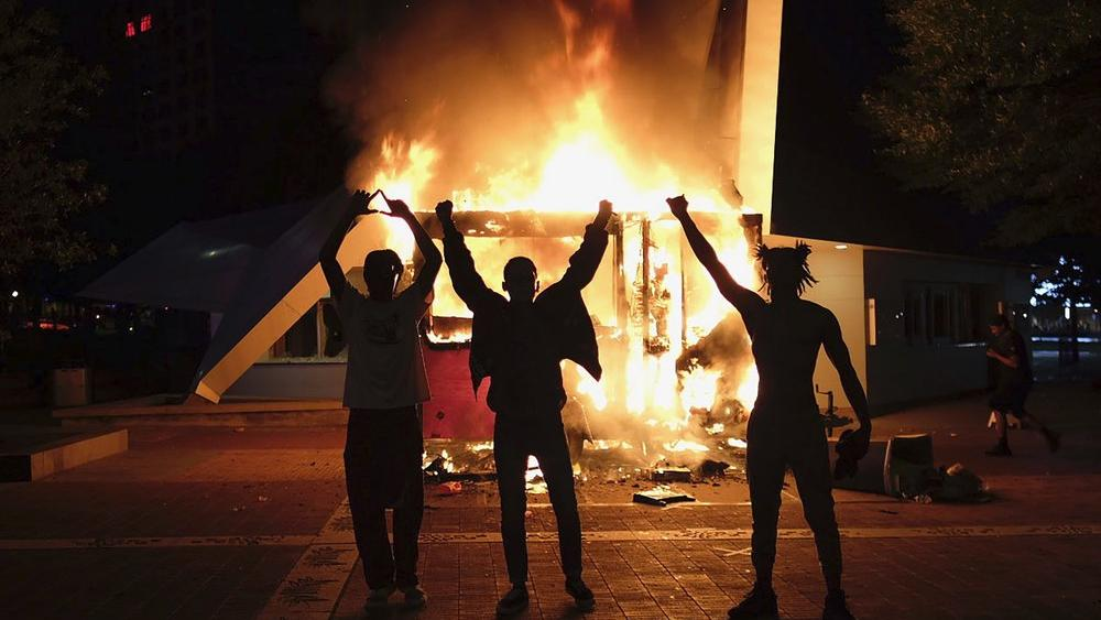 Protestors raise their hands in front of a burning vending cart on May 29, 2020, in Atlanta, Georgia (Be Gray/Atlanta Journal-Constitution via AP)