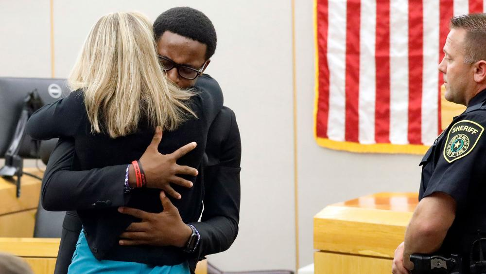 Botham Jean's younger brother Brandt Jean hugs convicted murderer Amber Guyger after delivering his impact statement to her after she was sentenced to 10 years in jail, Oct. 2, 2019. (Tom Fox/The Dallas Morning News via AP)