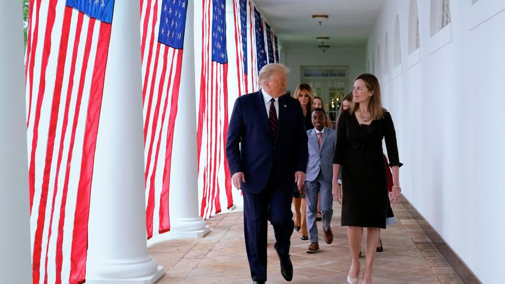 President Donald Trump walks along the White House Colonnade with Judge Amy Coney Barrett and her family, Sept. 26, 2020. (AP Photo/Alex Brandon)