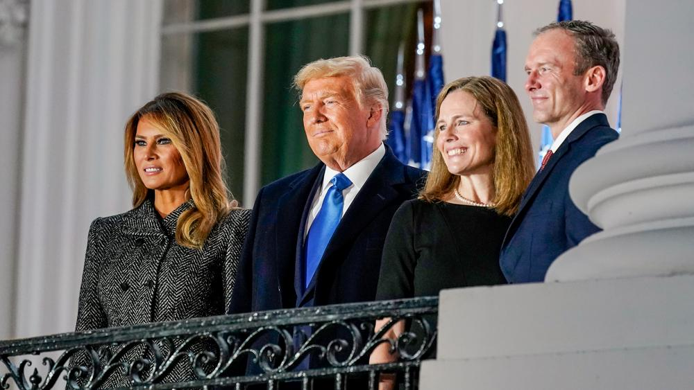 First lady Melania Trump, President Donald Trump, Amy Coney Barrett and Jesse Barrett, stand together after Supreme Court Justice Clarence Thomas administered the Constitutional Oath to Barrett, Oct. 26, 2020. (AP Photo/Patrick Semansky)