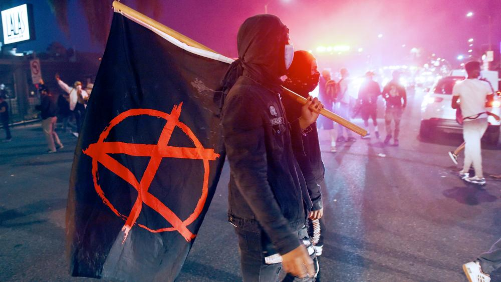 A man carries a flag depicting the anarchist symbol during a protest over the death of George Floyd, May 30, 2020, in Los Angeles. (AP Photo/Chris Pizzello)