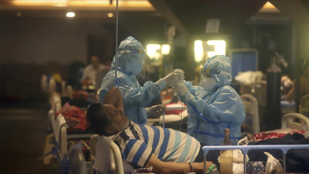 Health workers attend to COVID-19 patients at a makeshift hospital in New Delhi, India, Friday, April 30,