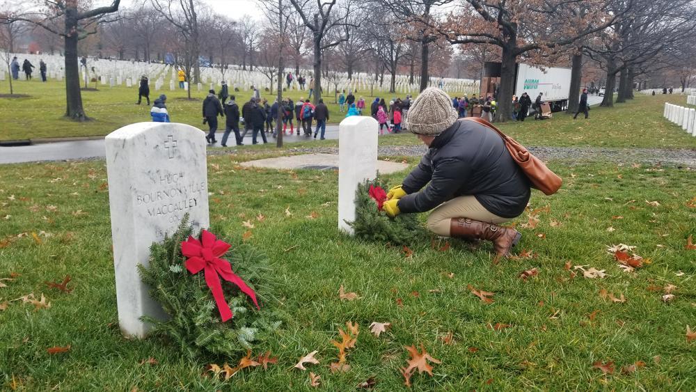 Volunteer Christina Tallmadge lays a wreath at a veteran's grave at Arlington National Cemetery. (Photo: Mike Lang, Jr.)
