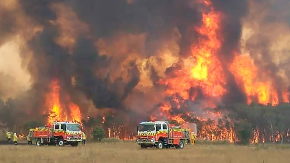 Wildfires burning across Australia's two most-populous states Tuesday trapped residents of a seaside town in apocalyptic conditions, destroyed many properties and caused fatalities. (Twitter@NSWRFS via AP)