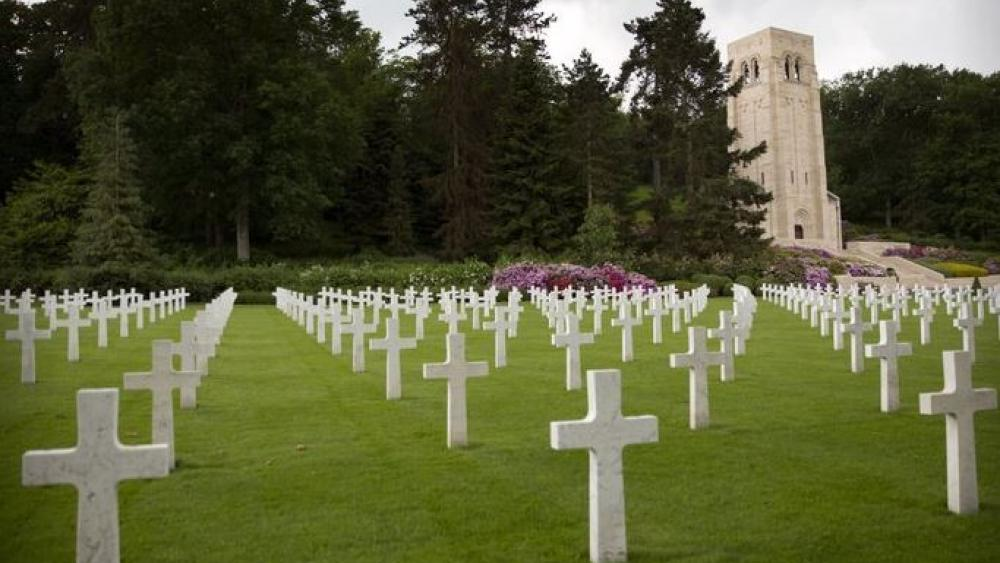 In this photo, a memorial chapel, surrounded by pine and oak trees, towers over the graves of World War I soldiers at the World War I Aisne Marne cemetery in Belleau, France.