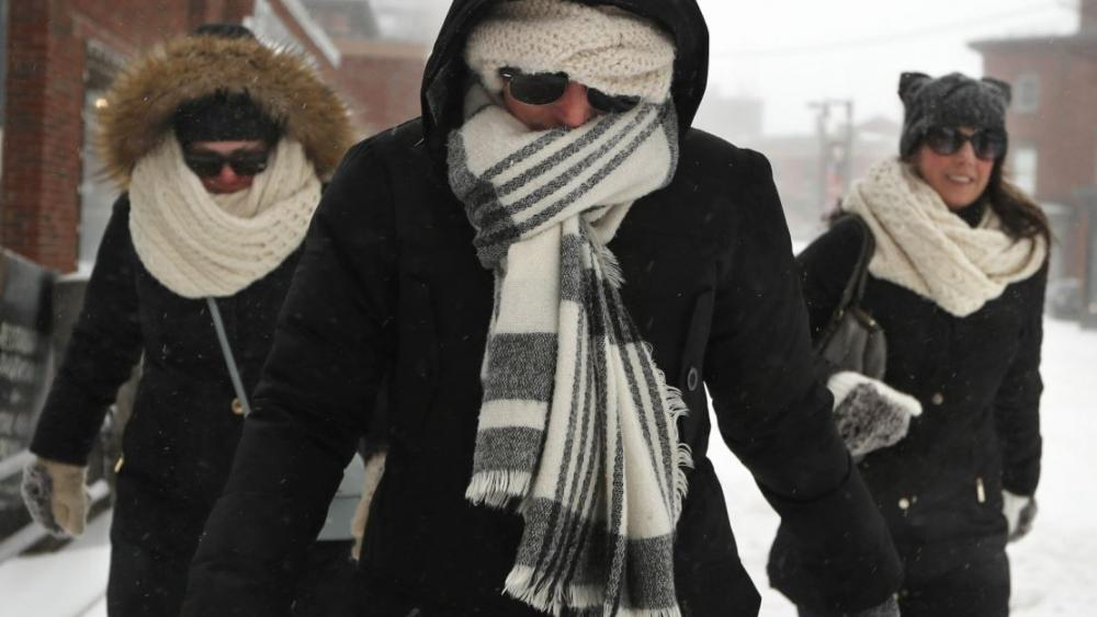Julia Beebe, center, Shannon Amore, left, and Jessica Lynch brave a winter storm to keep a lunch date, Sunday, Jan. 20, 2019, in Portland, Maine. (AP Photo/Robert F. Bukaty)
