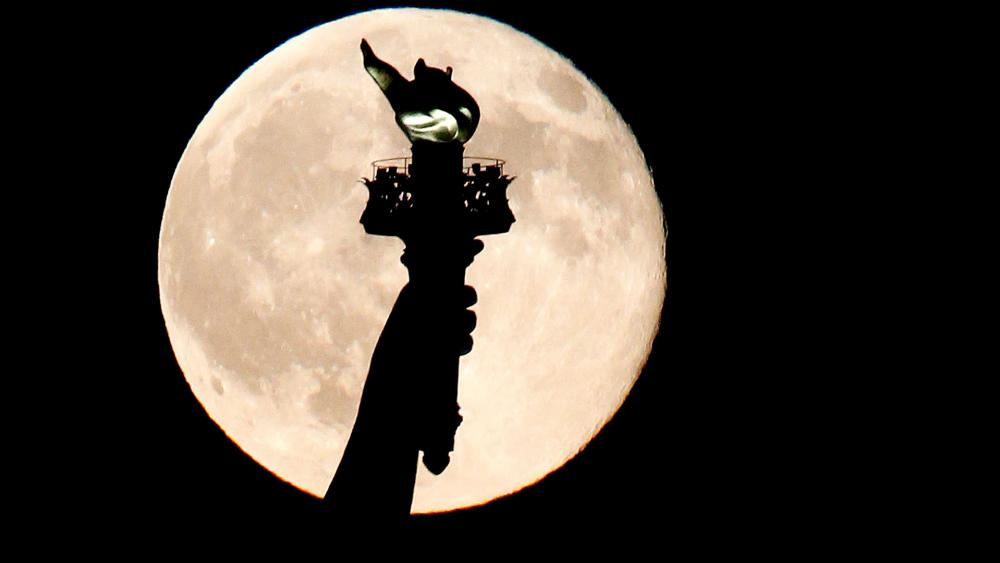In this July 31, 2015, file photo, a blue moon rises behind the torch of the Statue of Liberty. A blue moon happens when the moon rises in its full stage twice during the same month. (AP Photo/Julio Cortez, File)