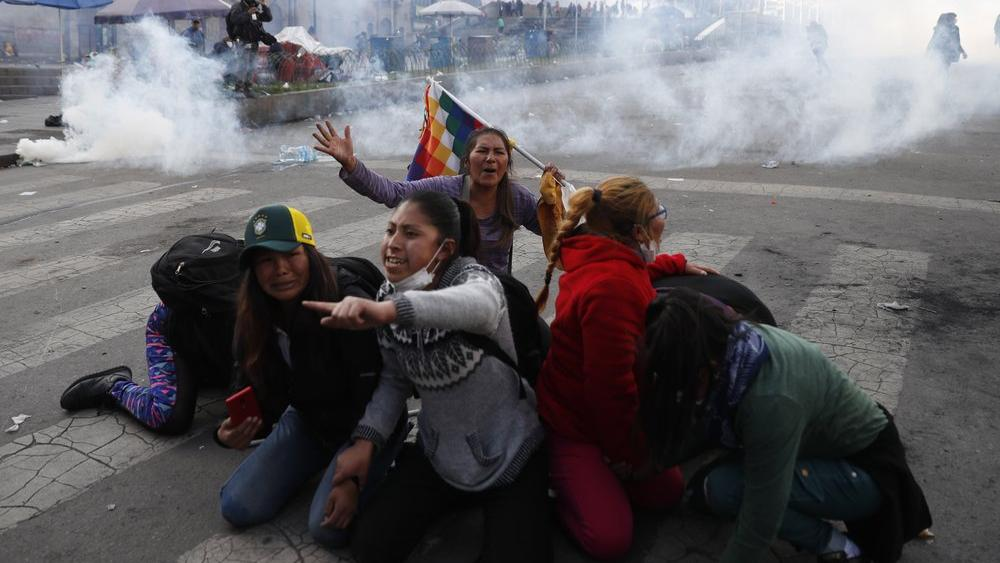 Supporter of former President Evo Morales protect themselves from tear gas launched by the police, in La Paz, Bolivia, Friday, Nov. 15, 2019. (AP Photo/Natacha Pisarenko)