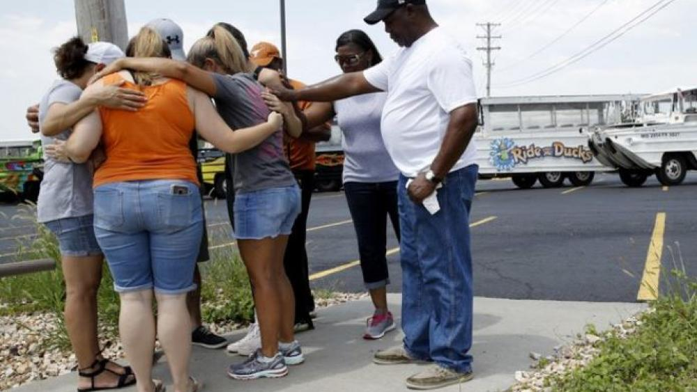 People pray outside Ride The Ducks, an amphibious tour operator involved in a boating accident on Table Rock Lake on Friday in Branson, Mo.