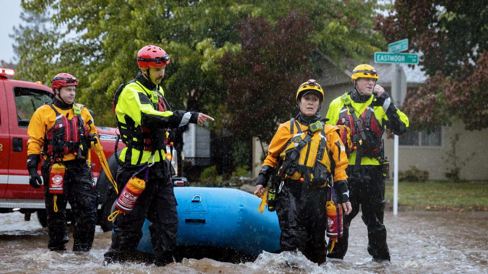 Santa Rosa firefighters check for residents trapped by floodwaters on Neotomas Avenue in Santa Rosa, Calif., on Oct. 24, 2021. (AP Photo/Ethan Swope)