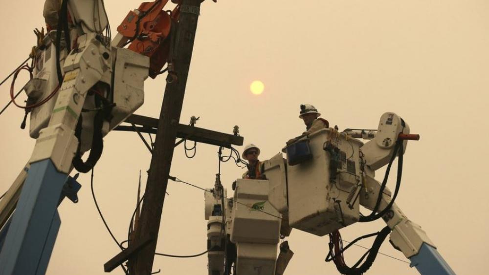 n this Nov. 9, 2018, file photo, Pacific Gas & Electric crews work to restore power lines in Paradise, Calif. (AP Photo/Rich Pedroncelli, File)
