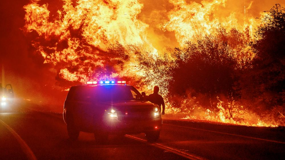 Flames lick above vehicles on Highway 162 as the Bear Fire burns in Oroville, Calif., on Wednesday, Sept. 9, 2020 (AP Photo/Noah Berger)