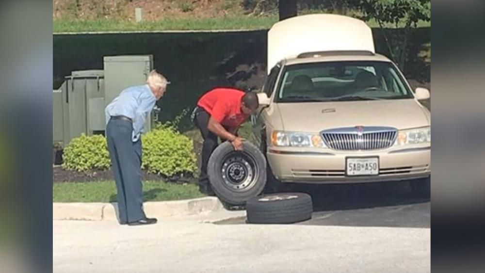 Chick-fil-A Manager Daryl Howard is seen helping Mr. Lee, a 96-year-old World War II veteran, change a tire. (Screenshot credit: Rudy Somoza/YouTube)