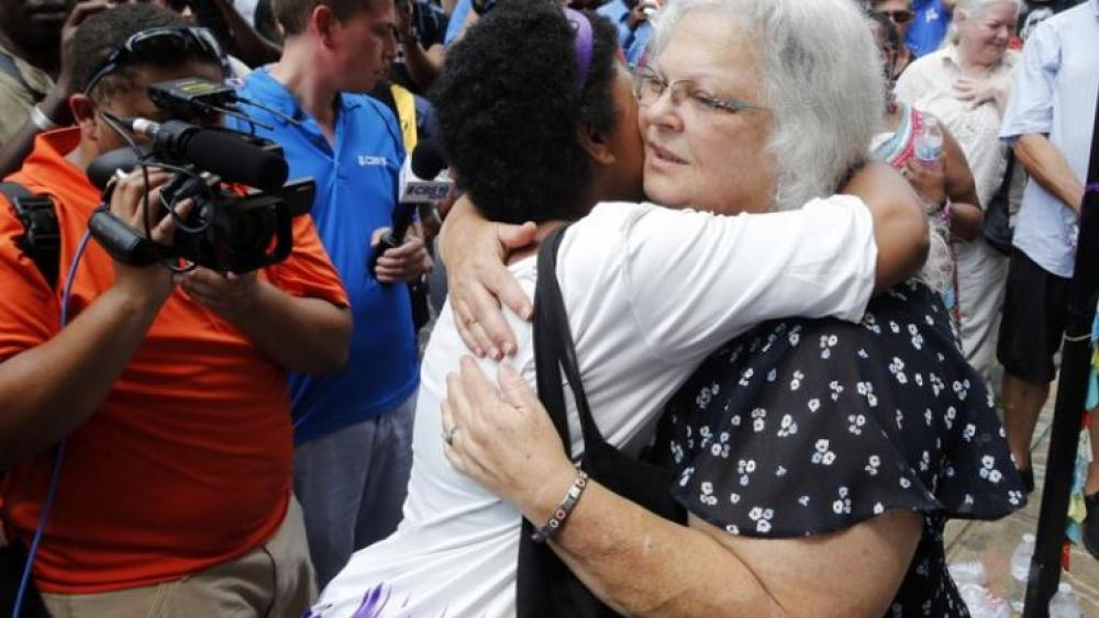 Susan Bro, mother of Heather Heyer who was killed during last year's Unite the Right rally, embraces supporters after laying flowers at the spot her daughter was killed in Charlottesville, Va.