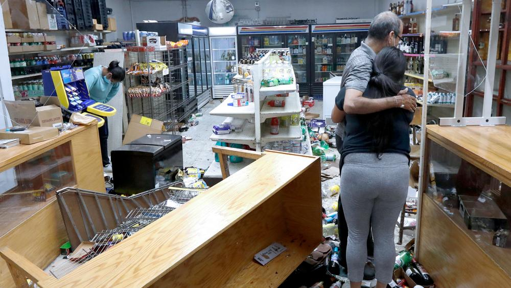 Yogi Dalal hugs his daughter Jigisha as his other daughter Kajal bows her head at the family store Aug. 10, 2020, after the family business was vandalized in Chicago. (AP Photo/Charles Rex Arbogast)