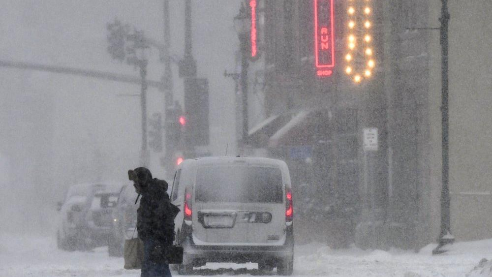 Heavy snow falls as people make their way home after work in downtown St. Cloud, Minn., Friday, Jan. 17, 2020. (Dave Schwarz/St. Cloud Times via AP)