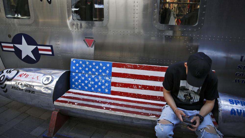 A man browses his smartphone on a bench with a decorated with U.S. flag outside a fashion boutique selling U.S. brand clothing at the capital city's popular shopping mall in Beijing, Monday, May 13, 2019. (AP Photo/Andy Wong)