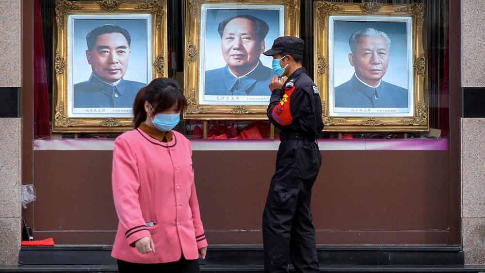 A security guard and worker walk past portraits of Chinese leaders, from left, Zhou Enlai, Mao Zedong, and Liu Shaoqi in the window of a photo studio in Beijing, April 15, 2020 (AP Photo/Mark Schiefelbein)