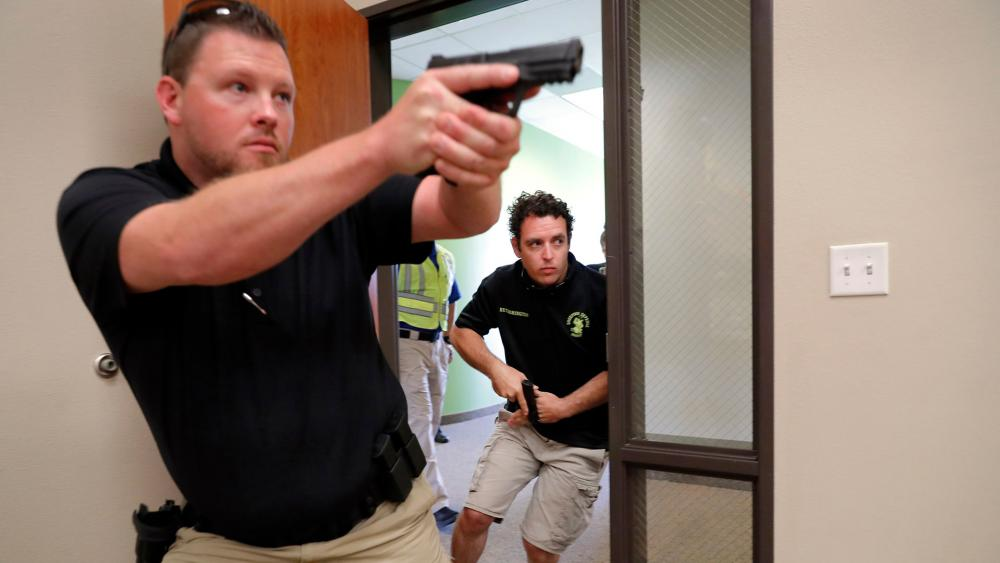 Trainees Chris Graves, left, and Bryan Hetherington, right, participate in a security training session at Fellowship of the Parks campus in Haslet, Texas. (AP Photo/Tony Gutierrez)