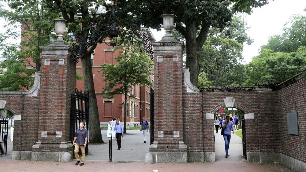 Pedestrians walk through the gates of Harvard Yard at Harvard University in Cambridge, Mass.(AP Photo/Charles Krupa, File)