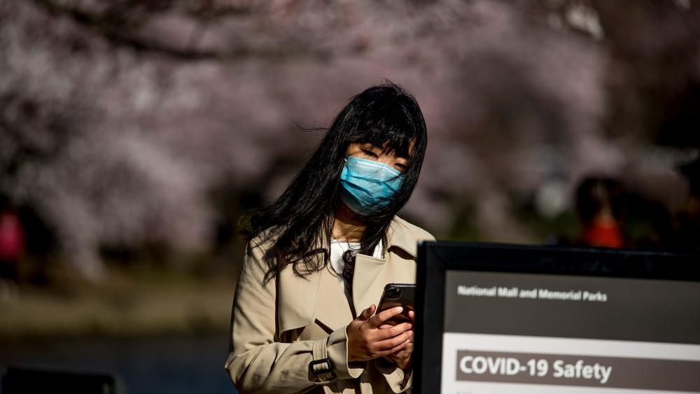 A woman wearing a mask stops to read coronavirus safety tips along an almost empty Tidal Basin lined with cherry blossoms that are about to peak, Wednesday, March 18, 2020, in Washington. (AP Photo/Andrew Harnik)
