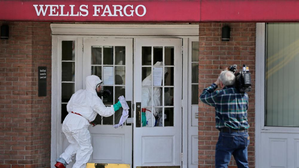 A cleaning crew disinfects a bank in New Rochelle, N.Y., Wednesday, March 11, 2020. State officials are shuttering several schools and houses of worship for two weeks in the New York City suburb (AP Photo/Seth Wenig)
