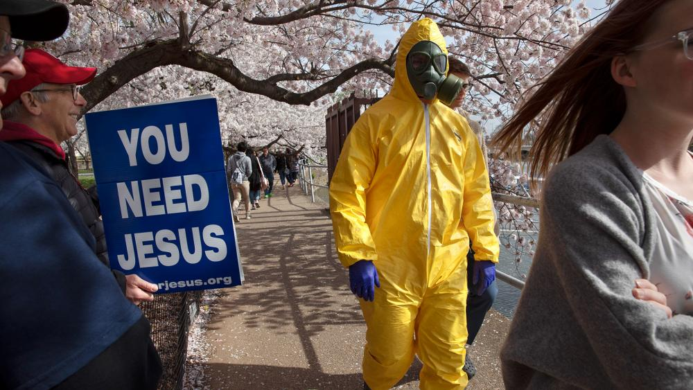 A 17-year-old wears a hazmat suit, gas mask, boots, and gloves as he walks under cherry blossom trees in full bloom along the tidal basin March 22, 2020, in Washington. (AP Photo/Jacquelyn Martin)