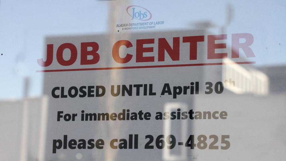A sign saying that the Jobs Center at the Alaska Department of Labor and Workforce Development office in midtown Anchorage, Alaska, is closed through the end of April. (AP Photo/Mark Thiessen)