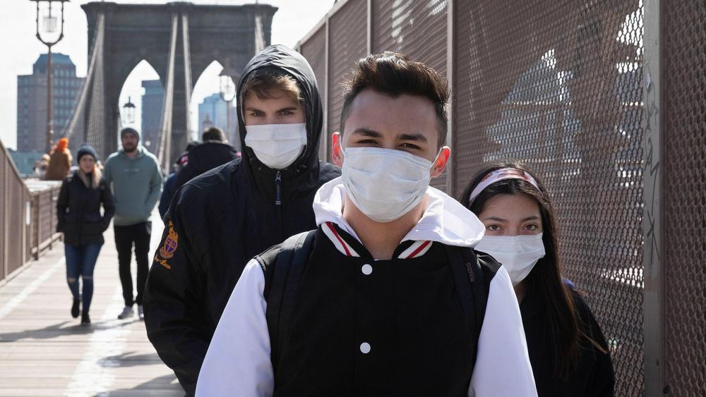 People wear masks as they cross the Brooklyn Bridge, Monday, March 16, 2020 in New York. (AP Photo/Mark Lennihan)
